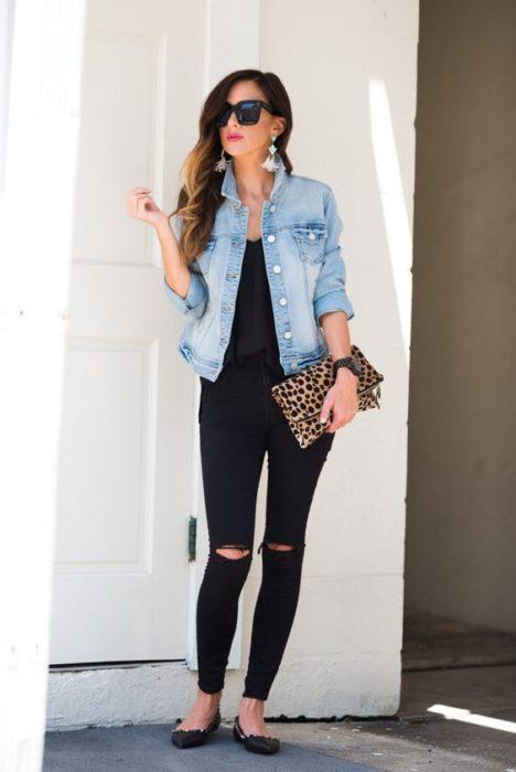 Chica de cabello largo y castaño con blusa y pantalón negros y chamarra de mezclilla con flatas negros