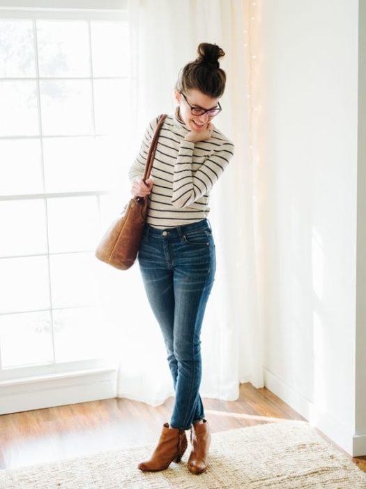 Chica con chongo y gafas con blusa blanca con rayas negras, jeans y botines cafés