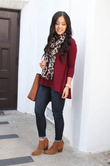 Chica de cabello largo suelto con saco guinda, jeans ocsuros y botines cafés