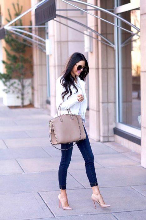 Mujer con saco blanco, bolsa beige, jeans oscuros y stilettos beige