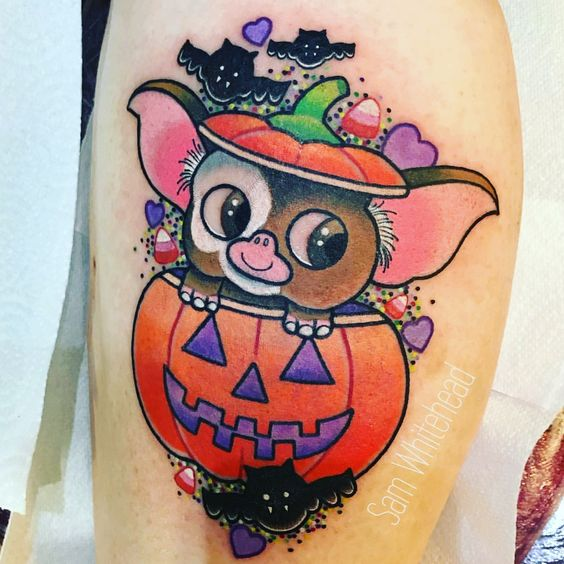 Tattoo in the shape of a gremlin coming out of a pumpkin