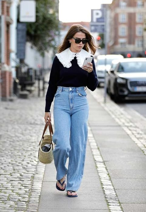 Slim girl walking on the street in black sweater with white bobo neck and jeans