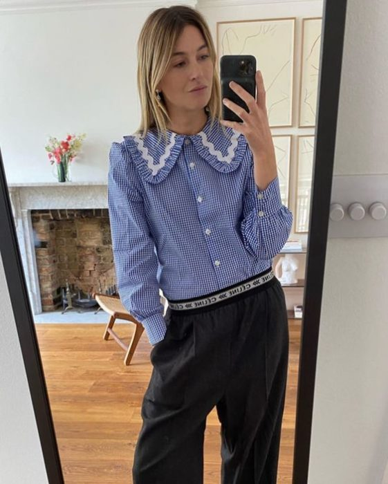 Blonde girl takes selfie in mirror with black pants and blue shirt with a bobo collar with pearls