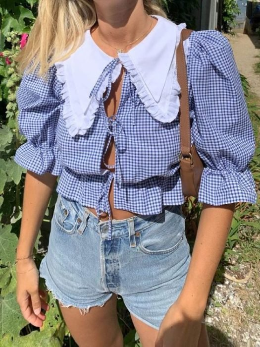 Girl in denim shorts with blue ruffle blouse with white bobo neck