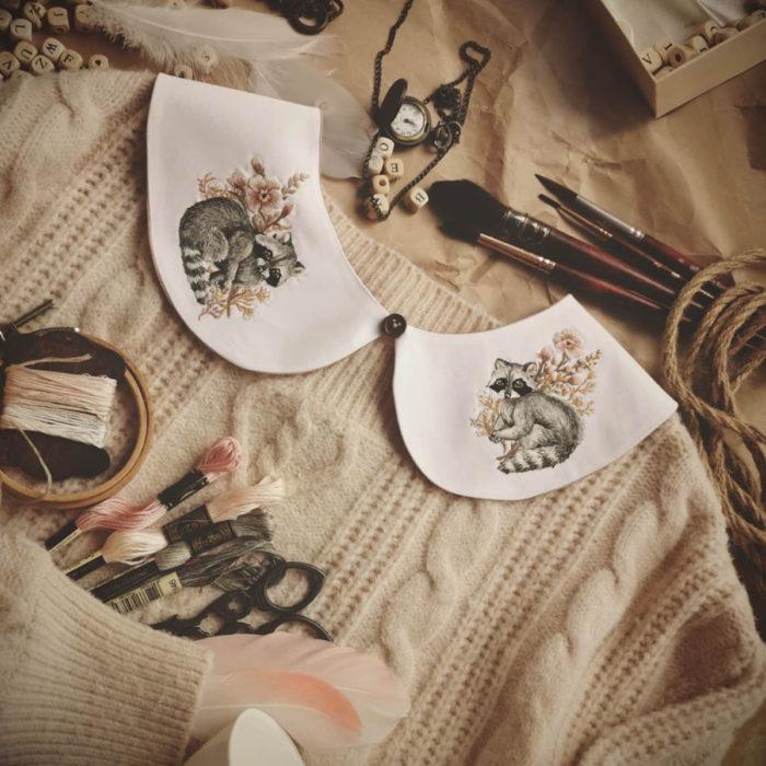 Amberry Lamb crea bonitos cuellos bordados de Halloween para vestidos y blusas; diseño de flores y mapache sobre tela blanca, suéter tejido beige, hilazas de colores