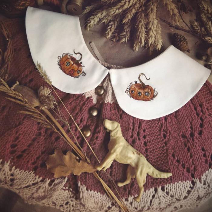 Amberry Lamb crea bonitos cuellos bordados de Halloween para vestidos y blusas; diseño de casas de calabaza sobre tela blanca, suéter tejido rojo con franjas cafés
