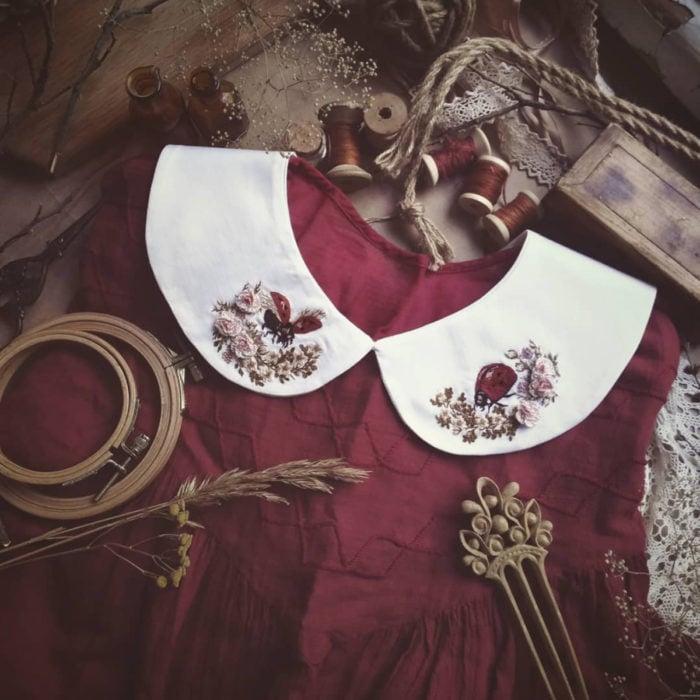 Amberry Lamb crea bonitos cuellos bordados de Halloween para vestidos y blusas; diseño de catarinas en flores sobre tela blanca, vestido rojo vintage