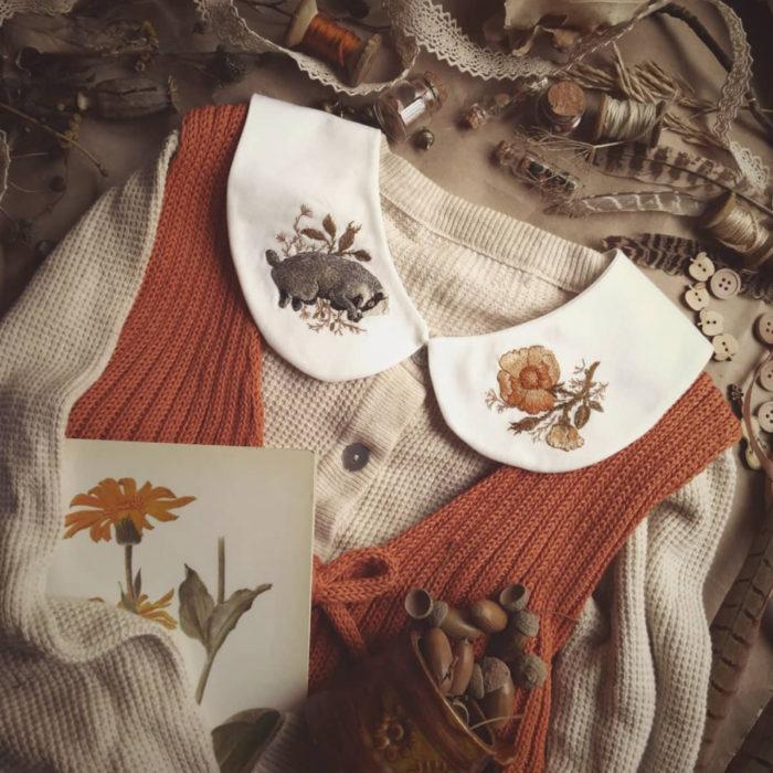 Amberry Lamb crea bonitos cuellos bordados de Halloween para vestidos y blusas; diseño de tejón con flores sobre tela blanca, suéter blanco, chaleco tejido anaranjado; dibujo de flores en técnica acuarela