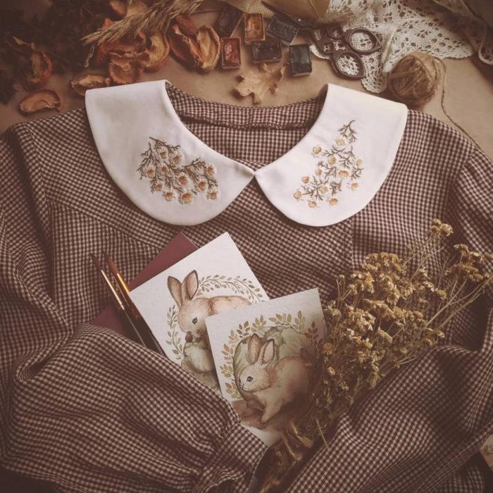 Amberry Lamb crea bonitos cuellos bordados de Halloween para vestidos y blusas; diseño de flores de manzanilla sobre tela blanca, vestido de cuadros vintage, pinturas de conejos en técnica acuarela