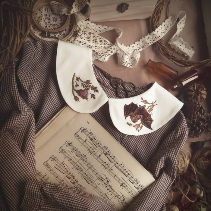 Amberry Lamb crea bonitos cuellos bordados de Halloween para vestidos y blusas; diseño de murciélago y flores en tela blanca, suéter tejido gris, partituras de música