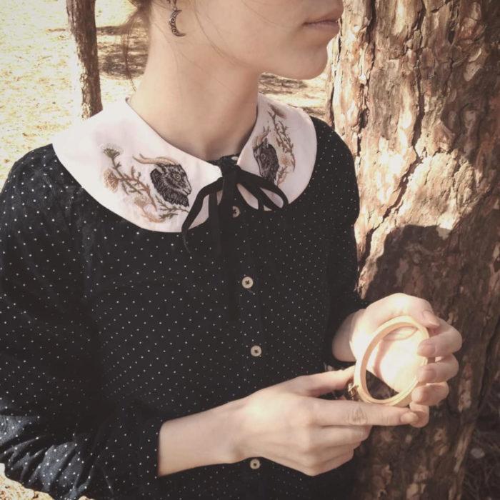 Amberry Lamb crea bonitos cuellos bordados de Halloween para vestidos y blusas; diseño de carnero sobre tela blanca, mujer al lado de un árbol usando vestido vintage de lunares blancos