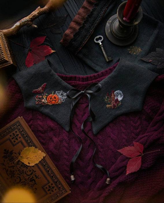 Little pin studio crea bonitos cuellos bordados de Halloween para vestidos y blusas; diseño de calabaza, murciélago, hongos, telaraña y casa embrujada sobre tela negra y suéter tejido rojo vino