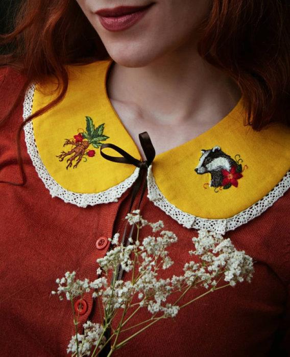 Little pin studio crea bonitos cuellos bordados de Halloween para vestidos y blusas; diseño de Hufflepuff, mandrágora, tejón sobre rela amarilla; mujer pelirroja con blusa anaranjada sonriendo