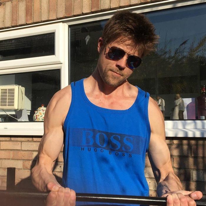 Nathan Meads doble de Brad Pitt cargando unas pesas para hacer ejercicio