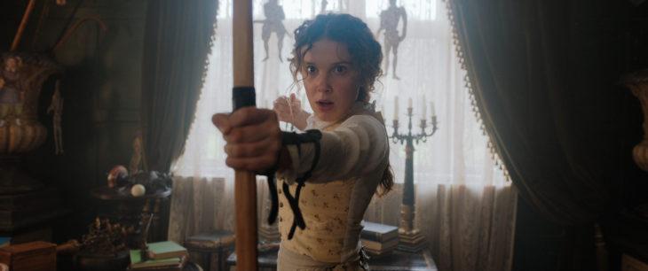Escena de la película Enola Holmes, en la que Enola dispara con el arco una flecha