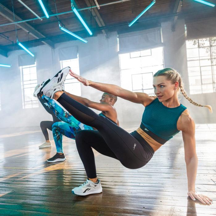 Mujer rubia haciendo ejercicio para brazos, piernas y abdomen con sus tenis Reebok