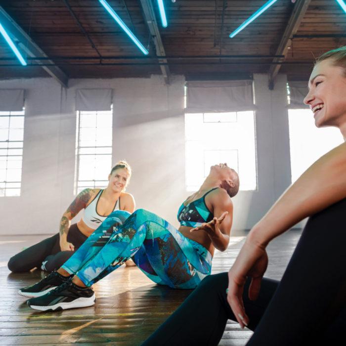 Mujeres amigas haciendo ejercicio, sentadas en el suelo riendo con sus tenis Reebok