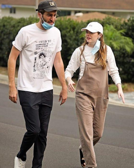 Emma Stone caminando con overol café y gorra blanca