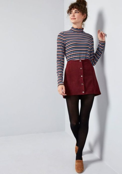 Girl wearing black tights, camel shoes, burgundy skirt and striped long-sleeved blouse