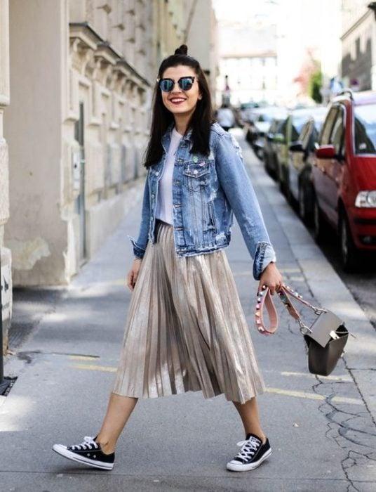 Chica caminando en la calle con falsa metálica gris, converse negros, blusa blanca y chamarra de mezclilla