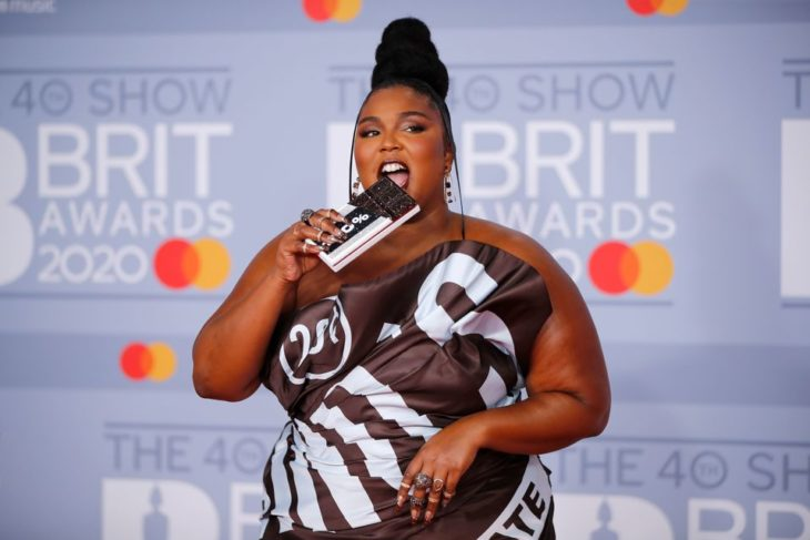 Lizzo wearing a chocolate print dress and pretending to eat her candy bar bag