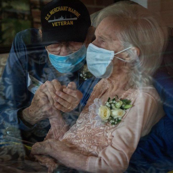 Abuelito sosteniendo la mano de su esposa mientras están juntos dentro de un automóvil