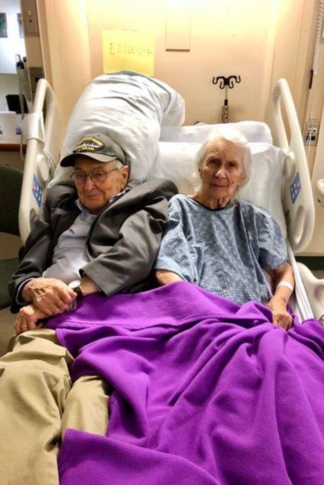 Pareja de abuelitos recostados en una cama dentro de un retiro de ancianos