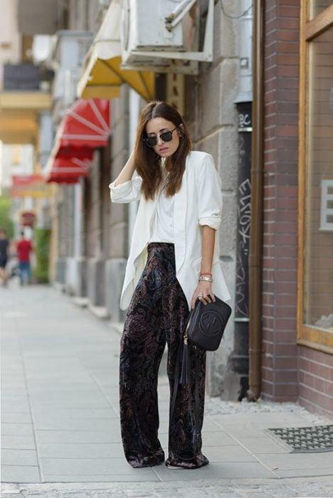 Chica de cabello largo con blusa y saco blancos y pantalón negro de terciopelo