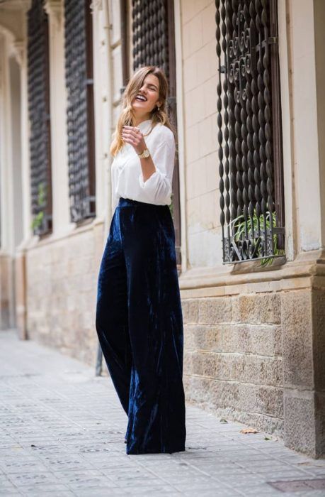 Chica rubia de cabello largo con camisa blanca y pantalón de terciopelo azul