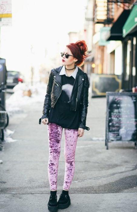 Red haired girl in denim jacket and pink velvet pants