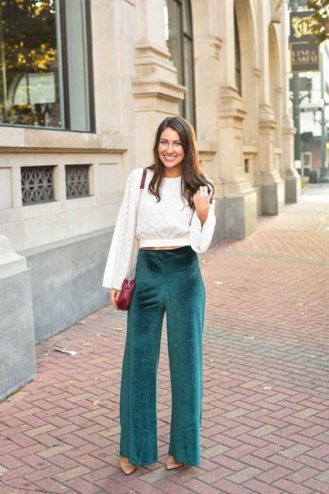 Mujer de cabello oscuro suelto con blusa blanca y pantalón verde esmeralda