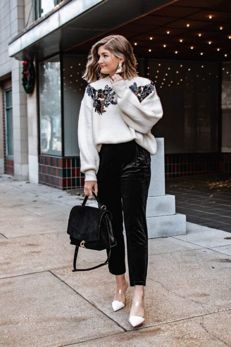 Blonde girl in black pants with white sweatshirt with details on the shoulders