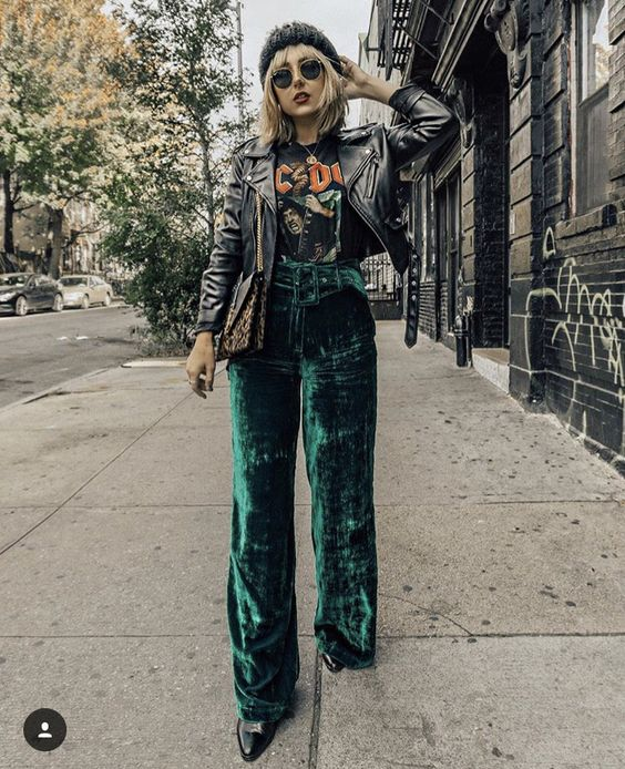 Blonde girl in black blouse and emerald green velvet pants with gray jacket