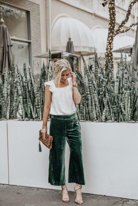 Blonde girl in white blouse with emerald green velvet pants