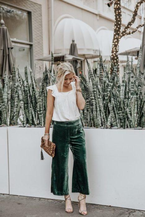 Chica rubia con blusa blanca con pantalón verde esmeralda de terciopelo