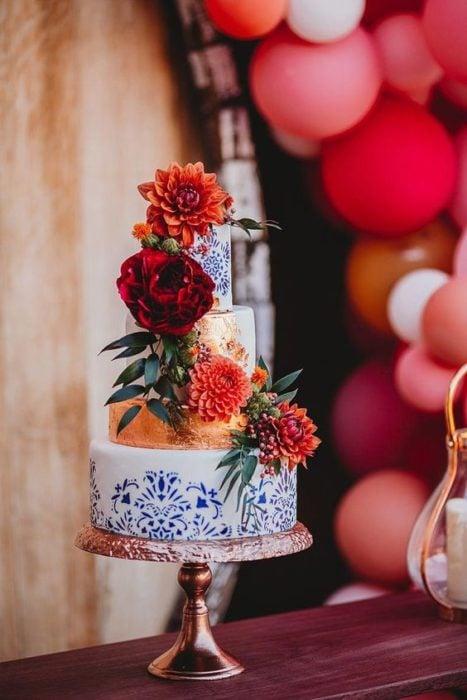 Pastel blanco con detalles azules y flores estilo mexicano