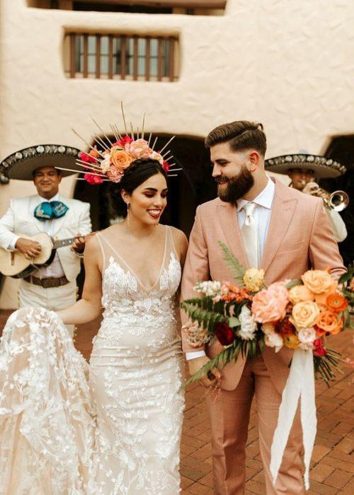 Novia y novio saliendo de templo con mariachis de fondo