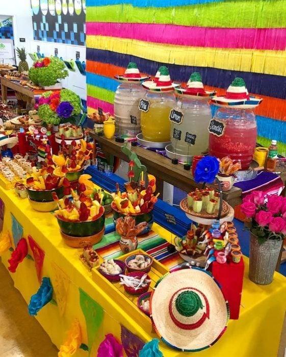 Mesa de dulces mexicana con dulces típicos y aguas frescas