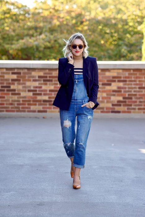 Short wavy hair blonde girl in denim overalls and white striped blouse with black and blue jacket