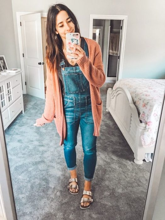 Girl taking selfie in front of mirror in denim overalls and salmon-colored cardigan