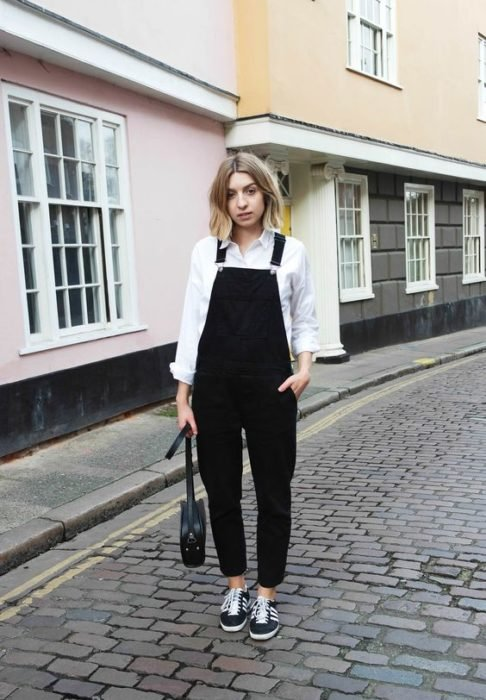 Short hair blonde girl in black overalls with white blouse