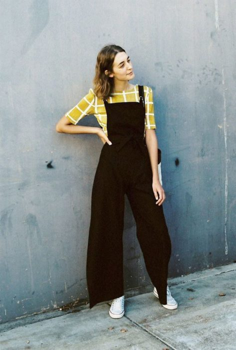 Girl posing with yellow blouse and black overalls