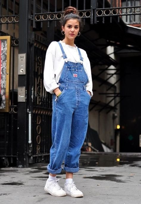 Girl with high bun, denim overalls and white blouse and tennis shoes