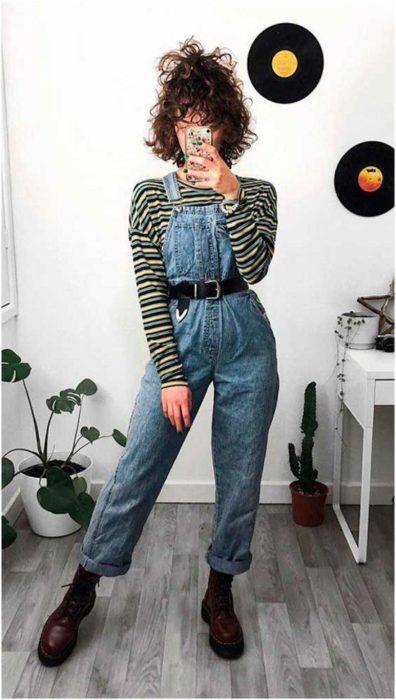 Chica tomándose selfie frente al espejo con overol de mezclilla y blusa de manga larga amarilla de rayas