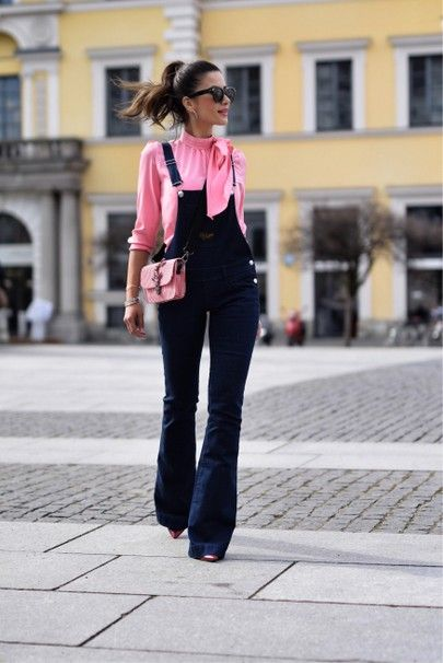 Tall slim girl in pink blouse and dark denim overalls