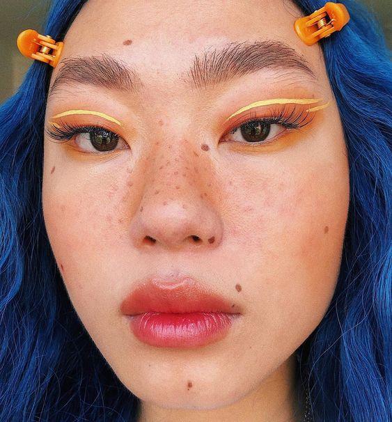 Chica asiática con sombra neón amarilla y naranj