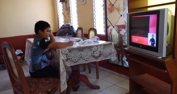 Jesús tomando clases por televisión con la TV que su maestra le dio
