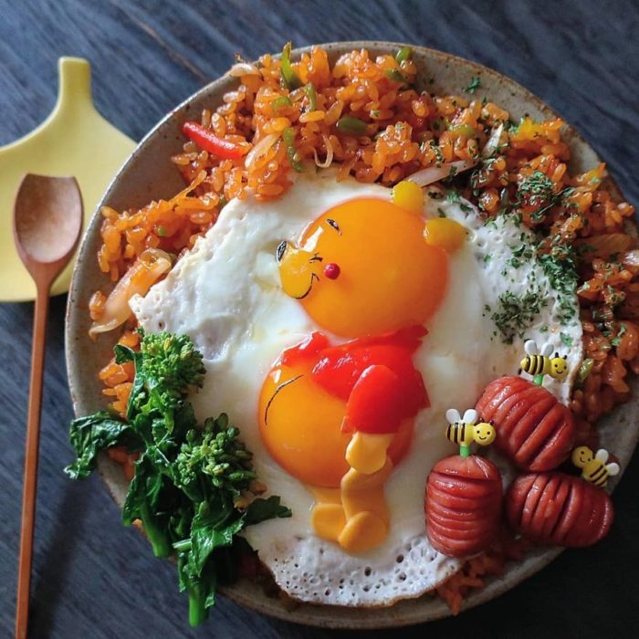 Platillo creador por la usuaria en Instagram Etoni Mama, plato de arroz con huevo estrellado en forma de Winnie-Pooh