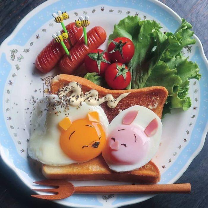 Platillo creador por la usuaria en Instagram Etoni Mama, huevo estrellados decorados como winnie pooh y puerquito
