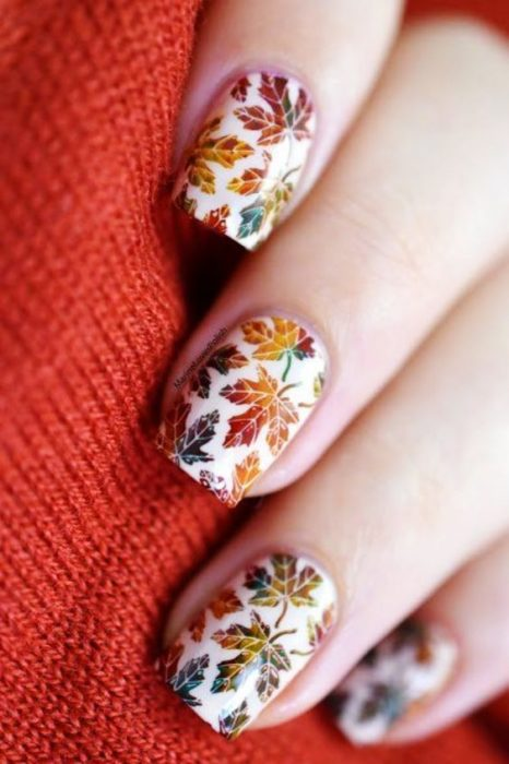 Manicura blanca con stickers de hoja de maple